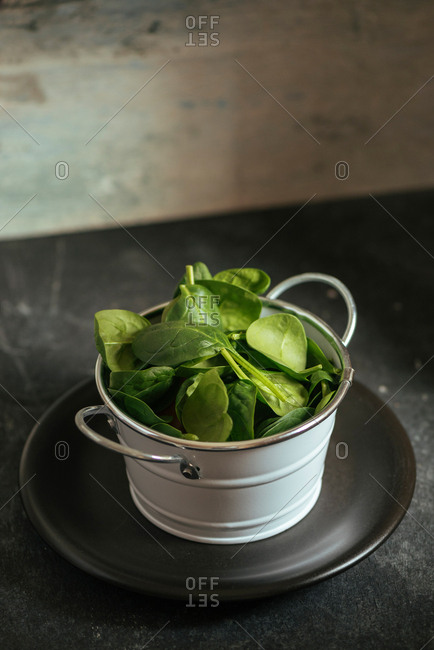 Fresh spinach on a rustic white metal crockery bowl, grunge background