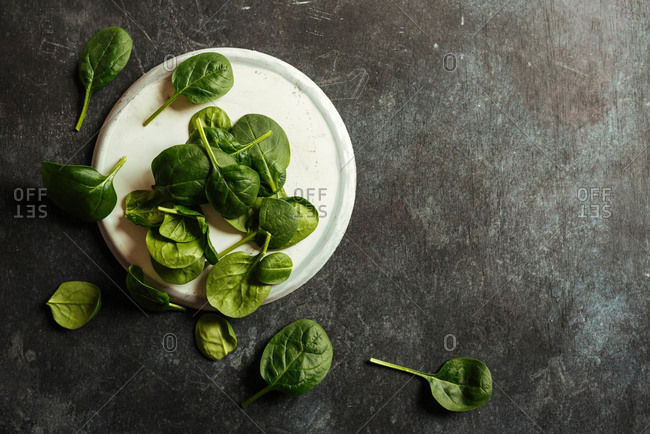 Fresh spinach on a rustic concrete crockery, grunge background