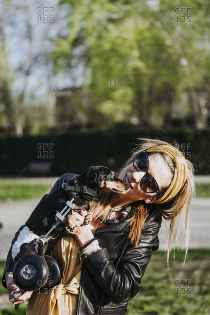 Smiling woman in sunglasses showing paralyzed handicapped Dachshund dog with wheelchair on street