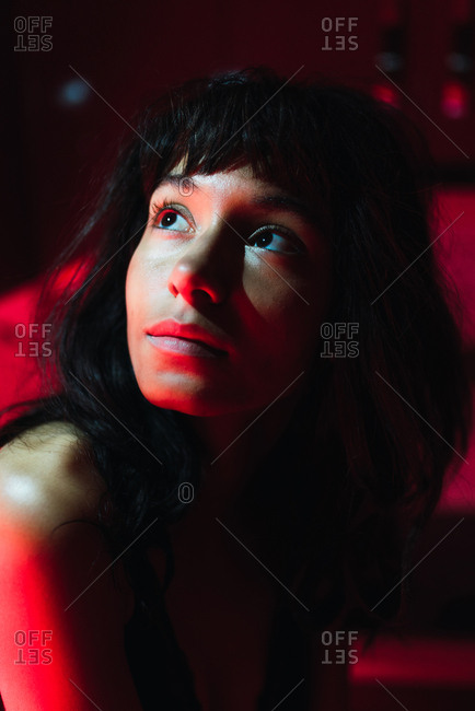 Sensual young brunette woman looking away and sitting in kitchen between redness