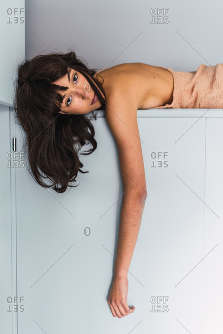 Side view of young woman on high shelf of wardrobe near bed in bedroom