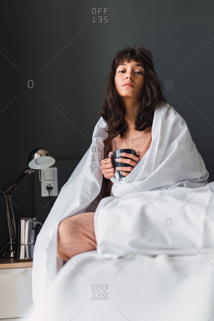 Young dozy woman with mug of drink in duvet sitting on bed in bedroom