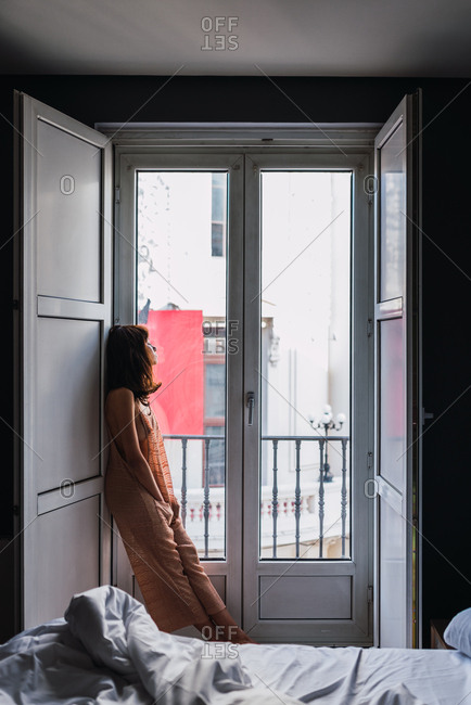 Young slim woman standing near big windows in the bedroom