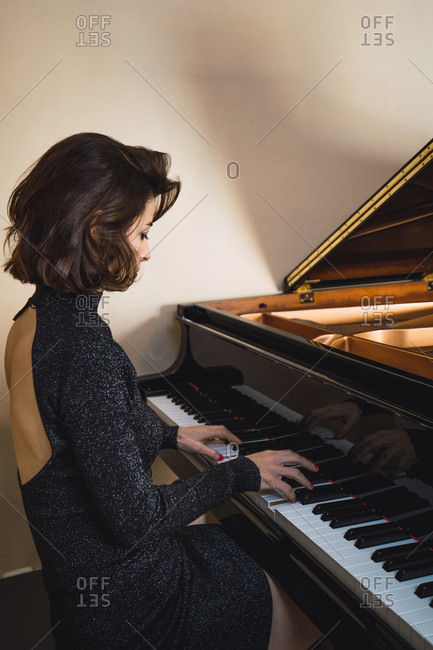 Young woman playing a piano at home