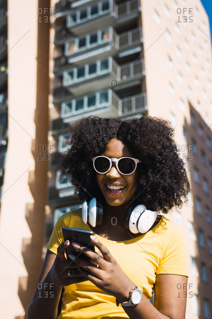 African-American girl listening to music with headphones from her phone