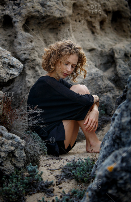 Young attractive charming woman sitting between rocks