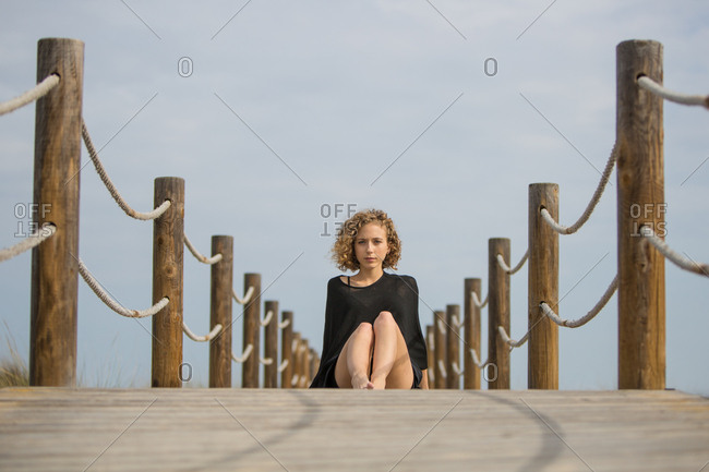 Young attractive charming woman looking at camera and sitting on footbridge on blue sky background