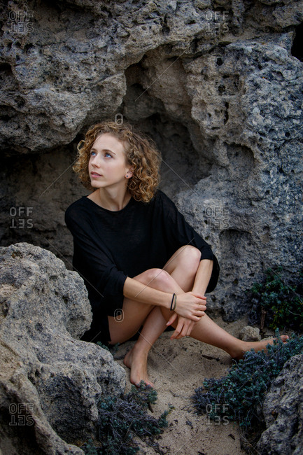 Young attractive charming woman looking away and sitting between rocks