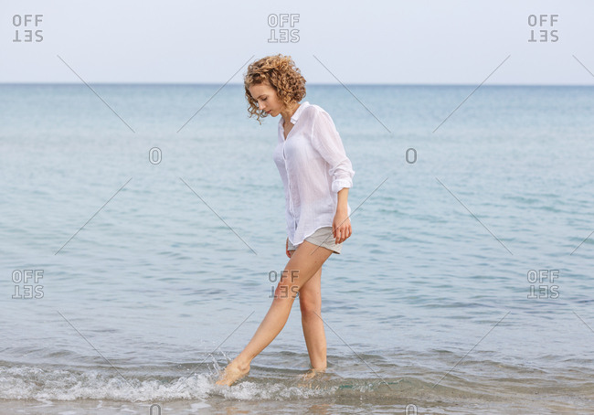 side view of Young attractive charming woman standing in sea near sand coast