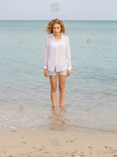 Young attractive charming woman looking at camera and standing in sea near sand coast