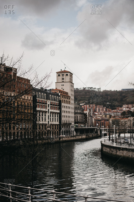 Gray clouds floating on sky over beautiful old buildings and canal with rippled water on dull day in Bilbao, Spain