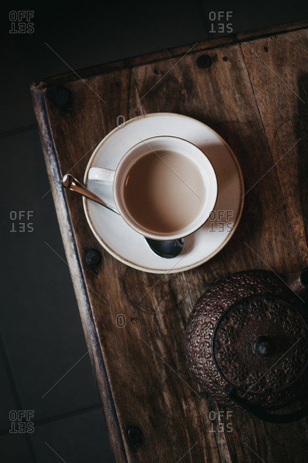 From above cup of fresh tea with milk placed on wooden tabletop near metal teapot in dark room