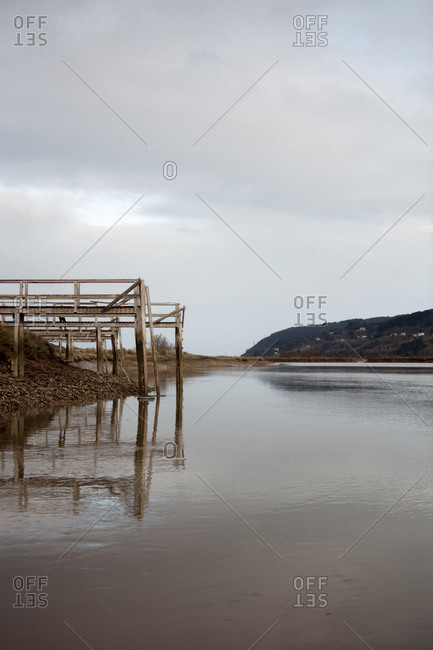 Aged wooden pier located on shore near calm water on cloudy day in countryside