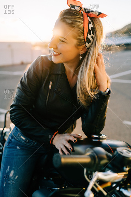 Pretty young woman in trendy outfit cheerfully smiling and looking away while sitting on modern motorbike on parking lot
