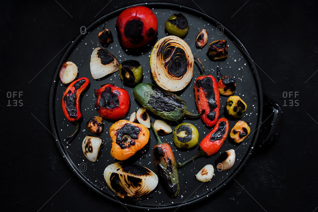 From above delicious roasted vegetables placed on black tray in kitchen