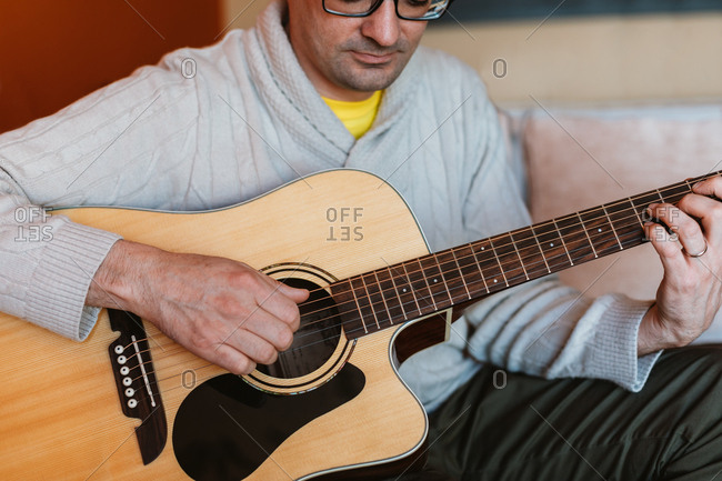 Man playing the guitar at home