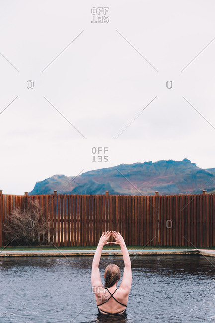 Back view of young woman resting in water of pool near cliffs on coast and stormy sea