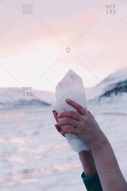 Crop hands of woman holding crystal rock near mountains and pink sky on blurred background