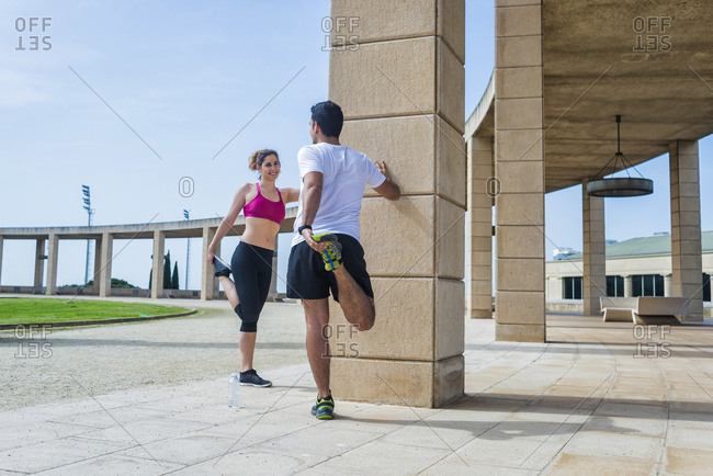 Back view of couple in sportswear stretching before running in park in sunny day