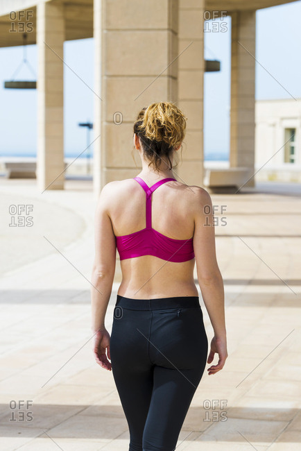 Back view of woman in sportswear getting ready before running in park in sunny day