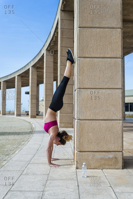 Side view of young slim woman in sportswear doing handstand near column in park