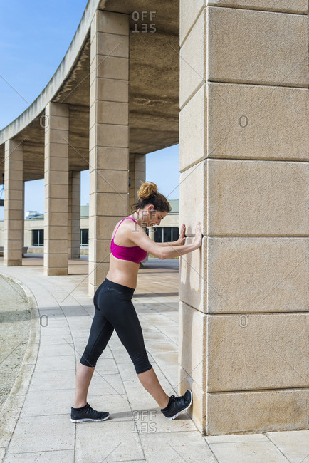 side view of woman in sportswear stretching before running in park in sunny day