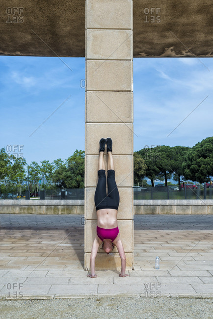 young slim woman in sportswear doing handstand near column in park