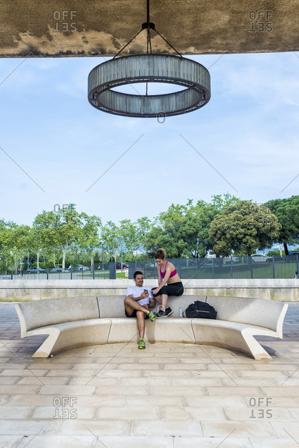 Couple in sportswear sitting and resting on bench with smartphone in park in sunny day