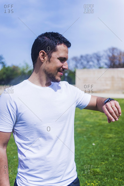 Young man in sportswear checking time on watch in park in sunny day on blurred background