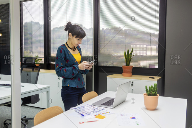 Pretty adult woman browsing in smartphone near laptop while working in modern office