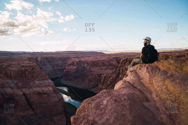 Back view of bearded guy with backpack looking at beautiful canyon and calm river on sunny day on West Coast of USA