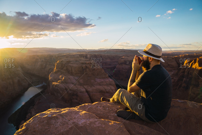 Side view of bearded guy in hat enjoying hot beverage and looking at setting sun while sitting near wonderful canyon on West Coast of USA