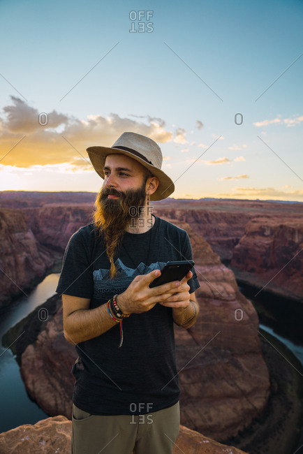 Handsome bearded man in hat on the mobile phone while standing against magnificent canyon and river during sunset on West Coast of USA