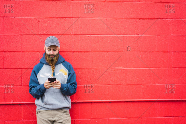 Attractive guy with braided beard browsing smartphone while leaning red wall on city street
