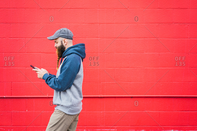 Side view of attractive guy with braided beard browsing smartphone while walking near red wall on city street