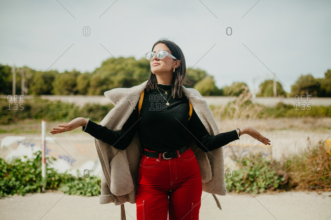 Lovely dreamy young woman in trendy outfit with jacket and looking away while standing on blurred background of beach