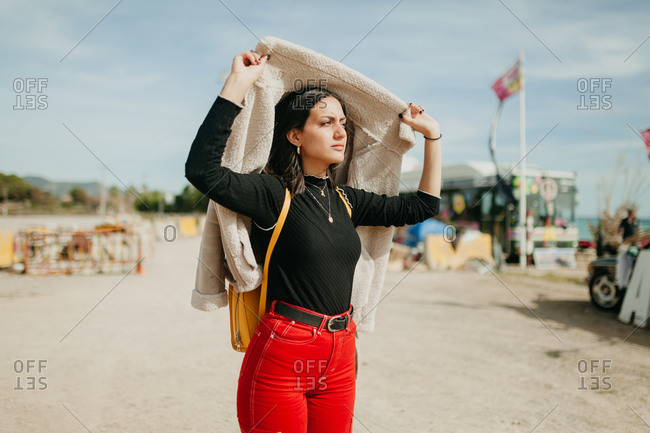 Lovely dreamy young woman in trendy outfit covering head with jacket and looking away while standing on blurred background of beach