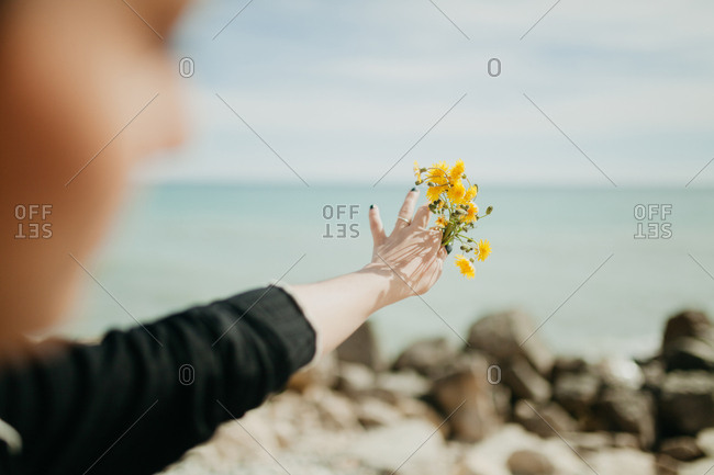 Back view of young woman throwing small yellow flowers into sea water while standing on cliff on sunny day