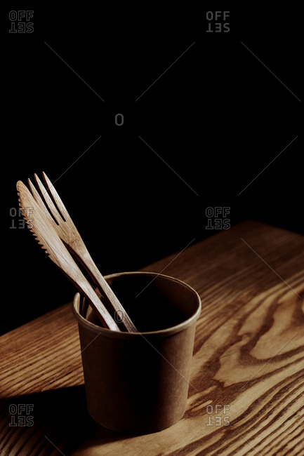 From above wooden fork and knife in cup on desk in dark room