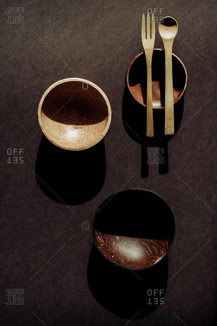 From above wooden spoon, fork near bowls on desk in dark room