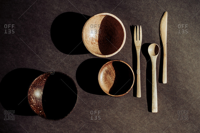From above wooden spoon, fork and knife near bowls on desk in dark room