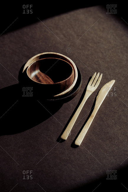 From above wooden fork and knife near bowls on desk in dark room