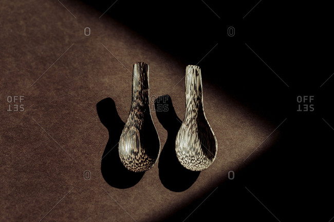 From above handmade wooden spoons on table in dark room
