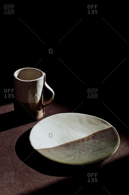 From above set of handmade natural dish and mug in dark room