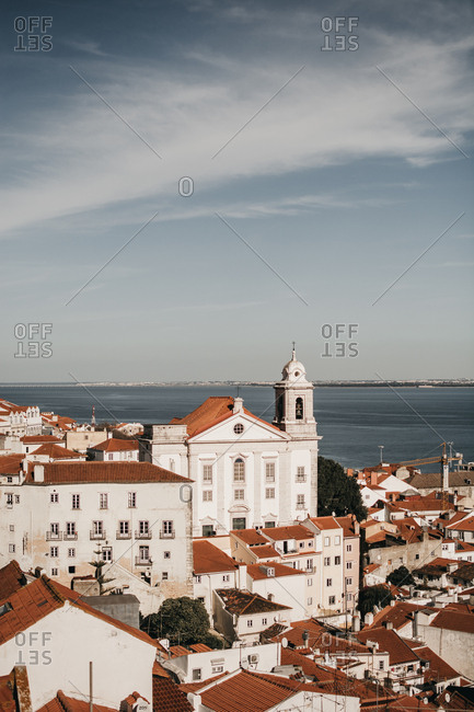 March 2, 2019: Amazing drone view of blue sky over tiled roofs of old houses and calm sea in Lisbon, Portugal