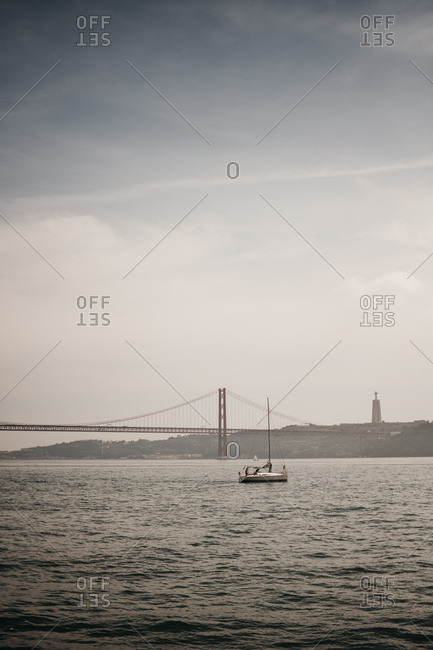 March 26, 2019: Amazing view of modern vessel floating on rippled sea old cloudy day near Lisbon, Portugal