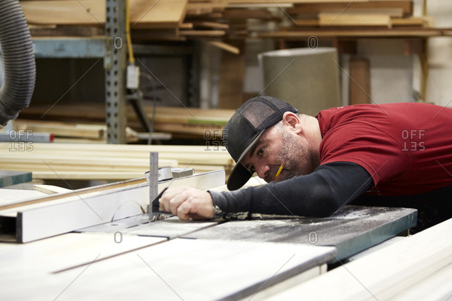 Carpenter using table saw in workshop, Seattle, Washington, USA