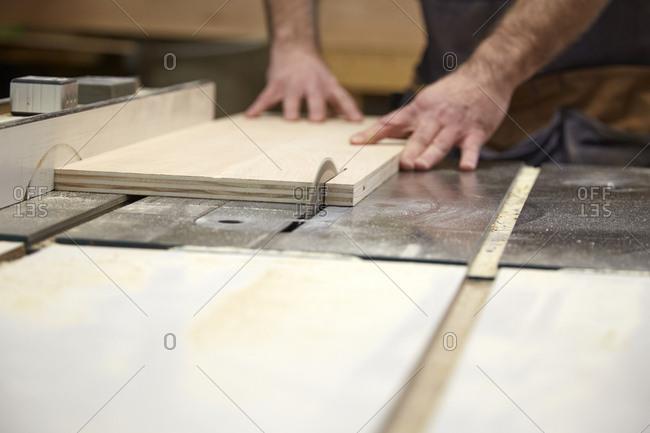 Carpenter using table saw in workshop, Seattle, Washington, USA