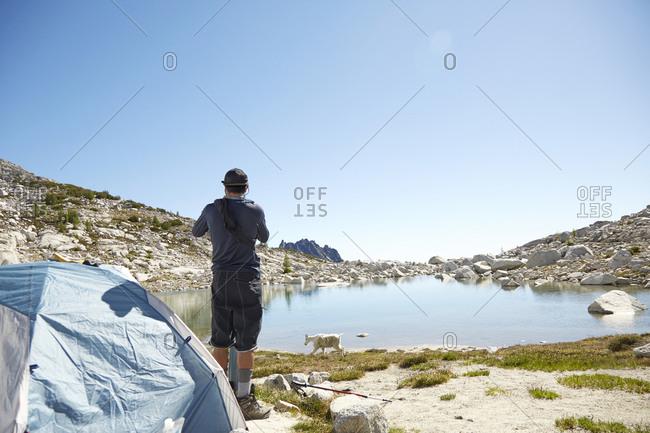 Man standing at tent at campsite near rural lake, Leavenworth, Washington, USA
