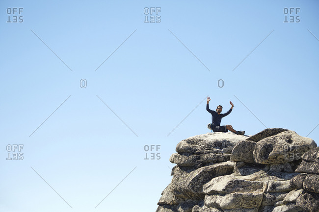 Hiker cheering on rocky hilltop under blue sky, Leavenworth, Washington, USA